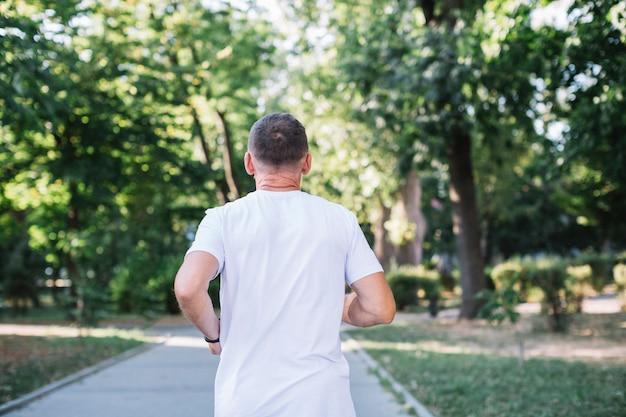 Oude man in witte t-shirt uitgevoerd in een park Gratis Foto