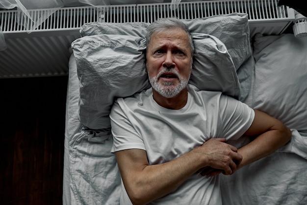Oude man is gestrest door ziek te worden op bed, hand in hand op de borst, hij kreeg de diagnose hoge bloeddruk en kanker. Premium Foto