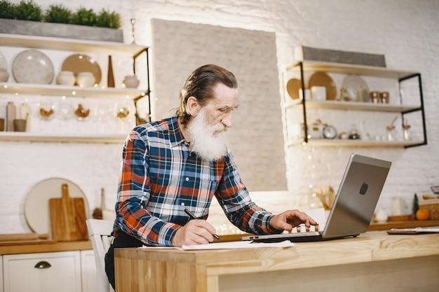 Oude man met laptop. grootvader zit in een kerstversiering. Gratis Foto