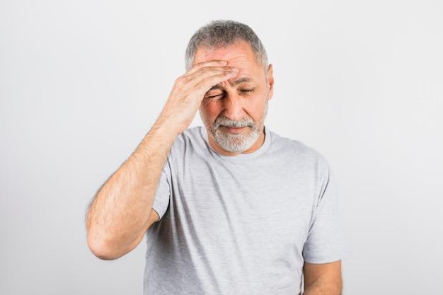 Oude man met pijn die zijn hoofd vasthoudt Gratis Foto