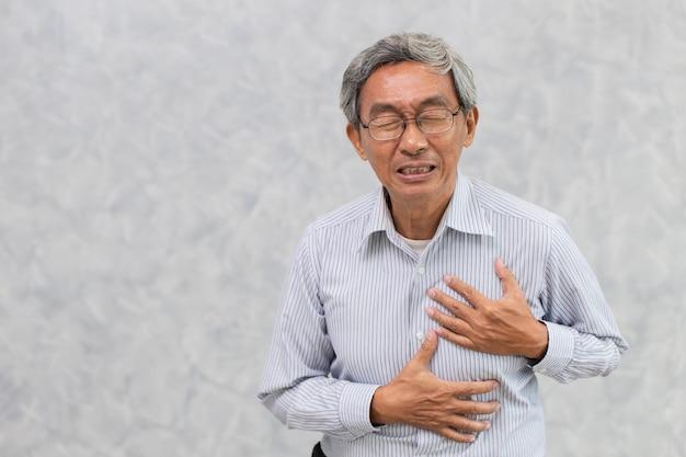 Oude man verf van hartaanval hand dekking borst met kopie ruimte Premium Foto
