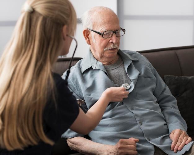 Oude man verzorgd door verpleegster Premium Foto