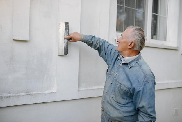 Oude mens die zich dichtbij de bouw met reparatiehulpmiddelen bevindt Gratis Foto