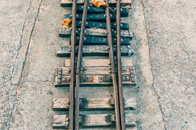 Oude miniatuur treinsporen bij zonsondergang. Premium Foto
