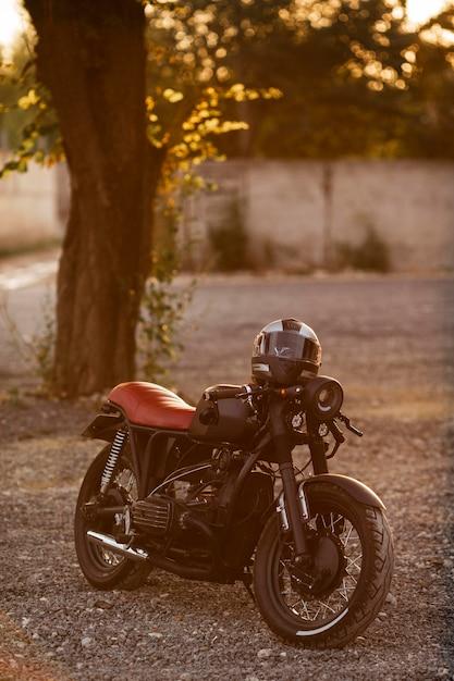 Oude motorfiets met helm buitenshuis Gratis Foto