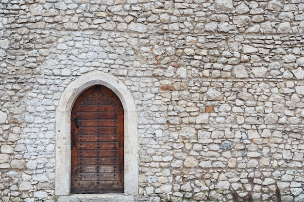 Oude muur en de voordeur in het middeleeuwse kasteel in krakau Premium Foto