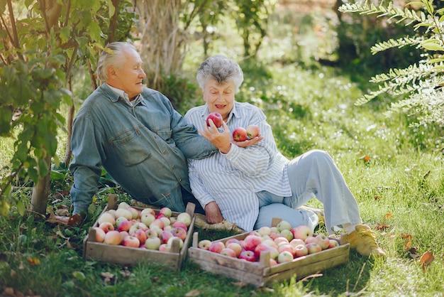 Oude paar zitten in een zomertuin met oogst Gratis Foto