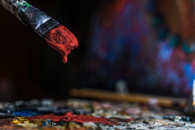 Oude penseel onderdompelen in rode kleur Gratis Foto