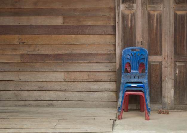Oude plastic stoelen geïsoleerd op houten muur achtergrond en