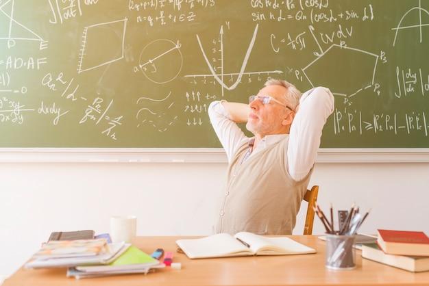 Oude professor ontspannen in de klas Gratis Foto