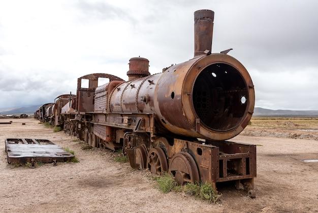 Oude roestige locomotief achtergelaten op een treinbegraafplaats. uyuni, bolivia Premium Foto