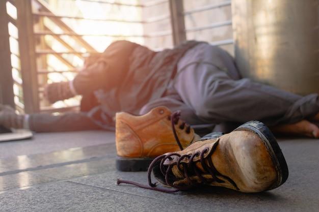 Oude schoenen en daklozen. dakloze man ligt op loopbrug in de stad. Premium Foto