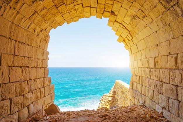 Oude stenen boog met uitzicht op de blauwe tropische zee. Premium Foto