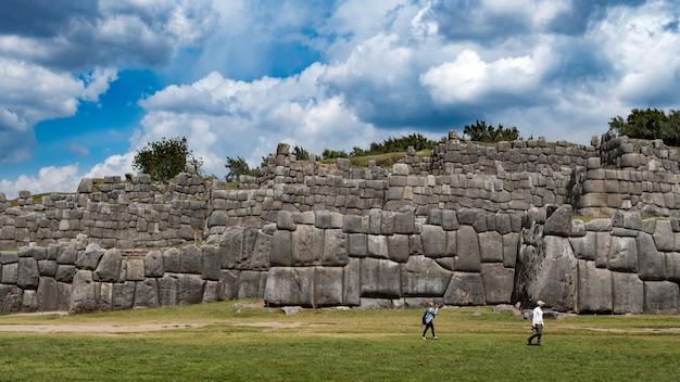 Oude stenen muur en toeristen in de buurt met een blauwe lucht Gratis Foto
