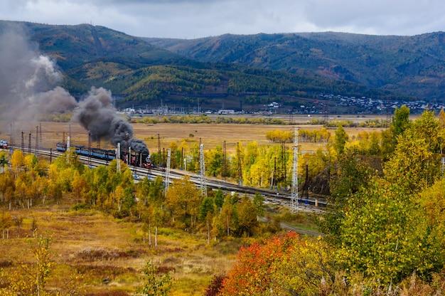 Oude stoomlocomotief in de circum-baikal railway met rook in de herfst Premium Foto