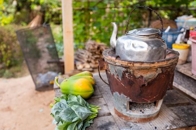 Oude thaise ketel op thais houtskoolfornuis met groene bladgroenten en gezette papaja Premium Foto