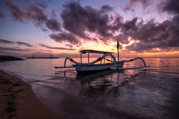 Oude traditionele jukung-vissersboot op kust bij kleurrijke zonsopgang Premium Foto