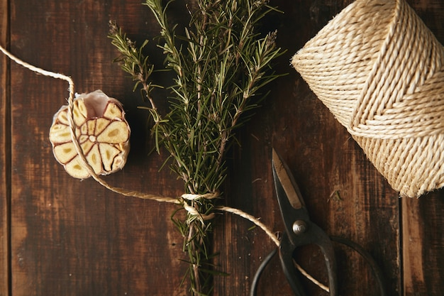 Oude tuin schaar, dik touw, knoflook en rozemarijn op grunge houten tafel. bovenaanzicht. Gratis Foto