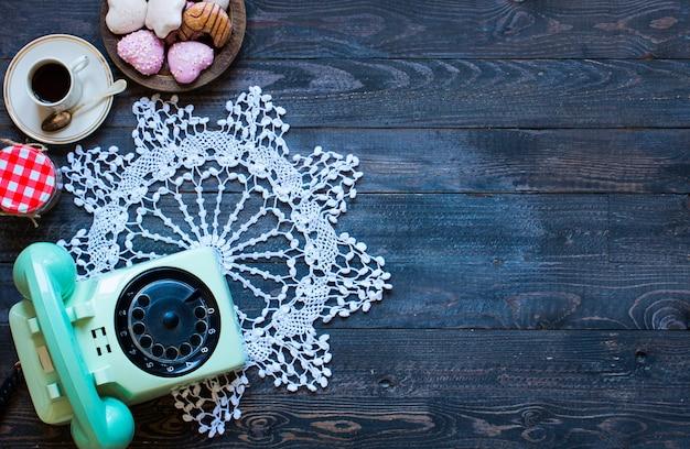 Oude uitstekende telefoon met biscottikoffie donuts op een houten achtergrond Premium Foto