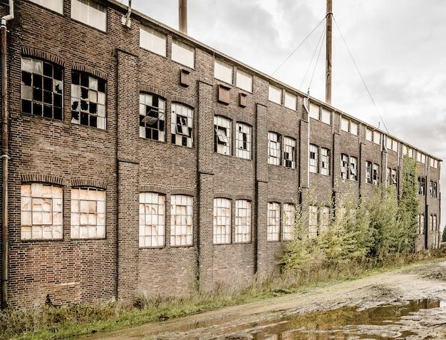 Oude verlaten stenen gebouw met gebroken ramen en een plas buiten Gratis Foto