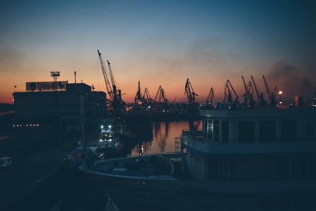 Oude verschepende haven en oud schip. lichten van de nacht Premium Foto