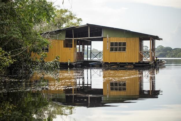 Oude verweerde gele houten hut aan het meer omgeven door prachtig groen Gratis Foto