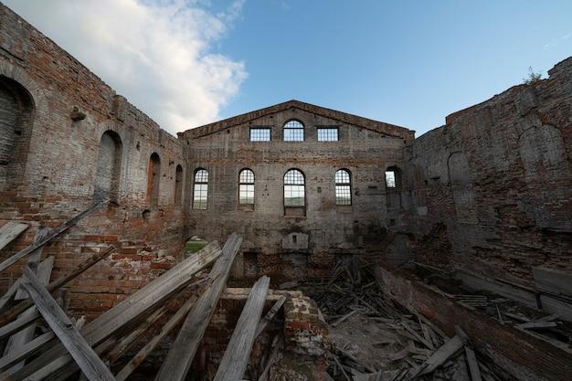 Oude verwoeste bakstenen gebouw zonder dak, onder een open blauwe hemel. Premium Foto