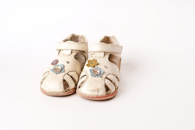 Oude vintage babysandalen op wit Premium Foto