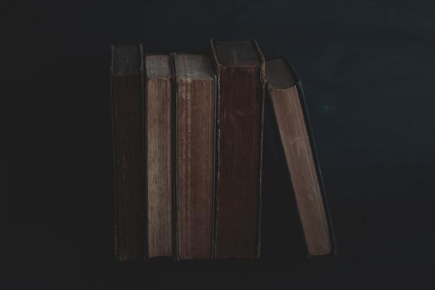 Oude vintage boeken op donker. Premium Foto