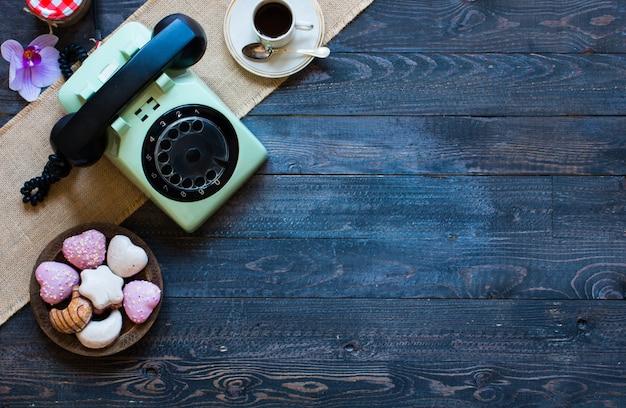 Oude vintage telefoon, met biscotti, koffie, donuts op een houten achtergrond Premium Foto