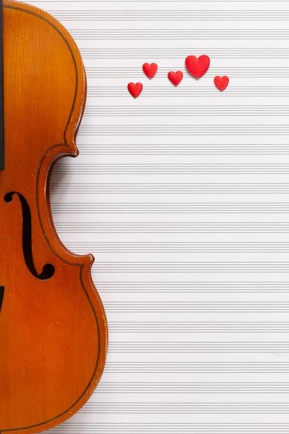 Oude viool en rode hartbeeldjes. bovenaanzicht, close-up, op witte achtergrond muziek papier Premium Foto