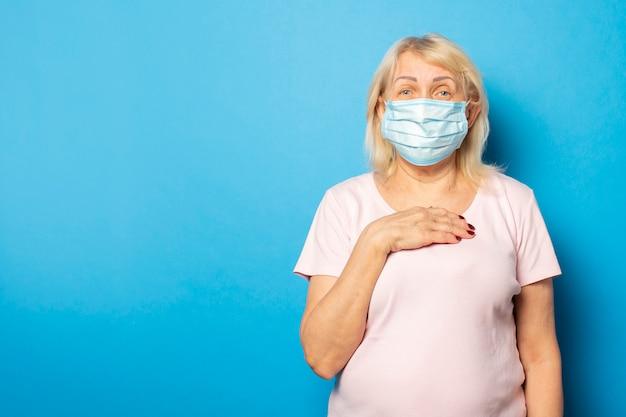 Oude vriendelijke vrouw in t-shirt en medische beschermend masker legde haar hand op haar borst tegen blauwe muur. emotioneel gezicht. conceptvirus, quarantaine, vuile lucht, pandemie. gebaar van angst, zorgen Premium Foto
