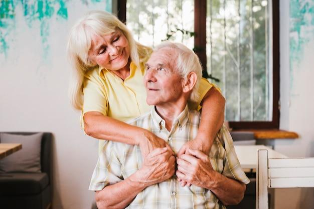 Oude vrouw die bejaardezitting thuis omhelst Premium Foto