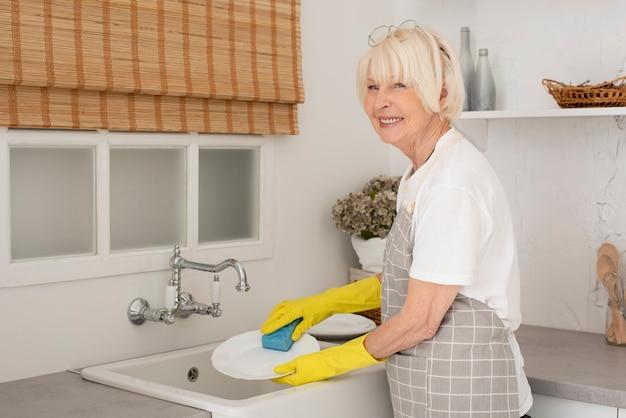 Oude vrouw die de schotels met handschoenen wast Gratis Foto