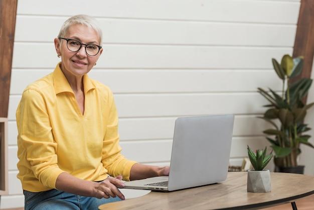 Oude vrouw die door internet op haar laptop kijkt Gratis Foto