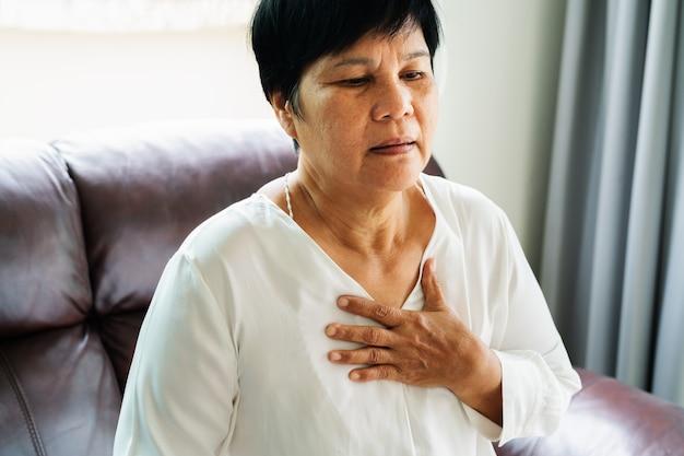 Oude vrouw die hartaanval heeft en haar borst grijpt Premium Foto