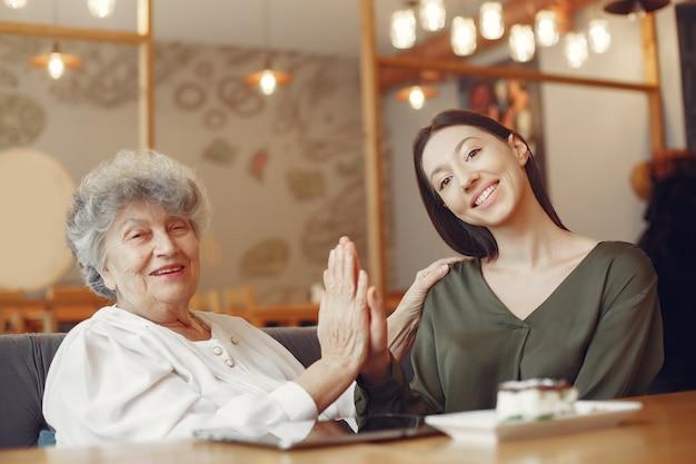 Oude vrouw in een café met jonge kleindochter Gratis Foto