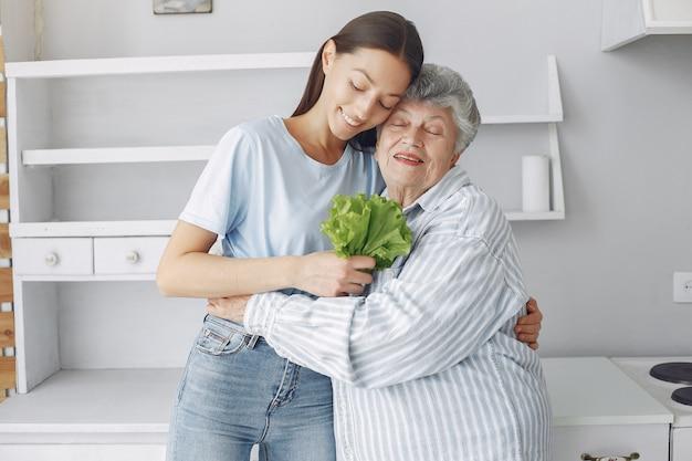 Oude vrouw in een keuken met jonge kleindochter Gratis Foto