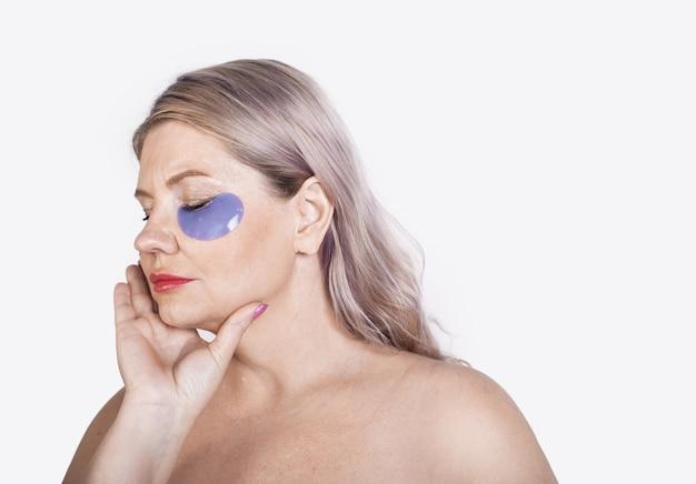 Oude vrouw met blond haar en hydrogel eye patches poseren met blote schouders Premium Foto