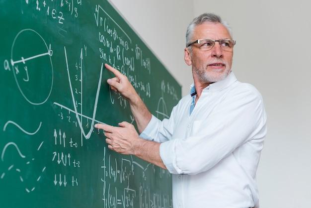 Oude wiskundeleraar die functie in klaslokaal uitvouwt Premium Foto