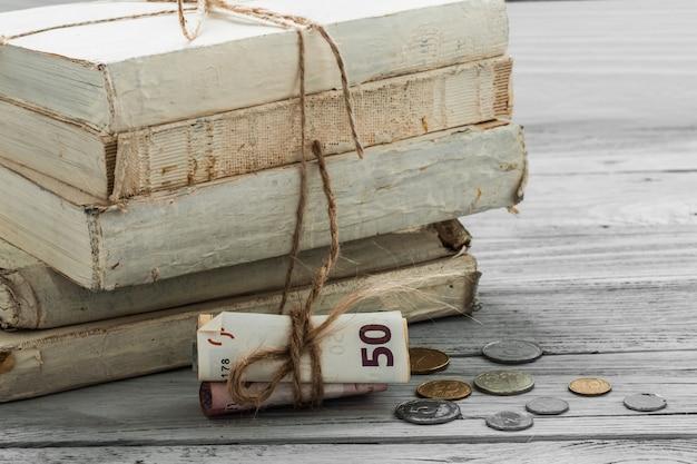 Oude witte boeken met geld en munten op houten achtergrond Gratis Foto