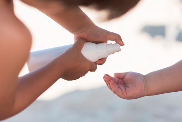 Ouder die suncream in de hand van het kind toepast Gratis Foto
