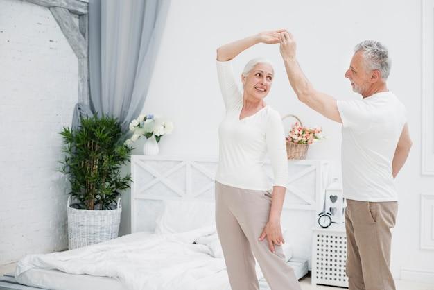 Ouder echtpaar dat in de slaapkamer danst Gratis Foto