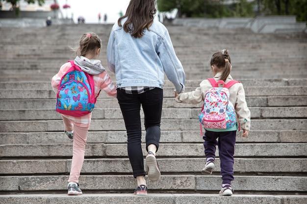 Ouder en leerling van de basisschool gaan hand in hand. moeder van twee meisjes met een rugzak achter de rug. begin van lessen. eerste dag van de herfst. Gratis Foto