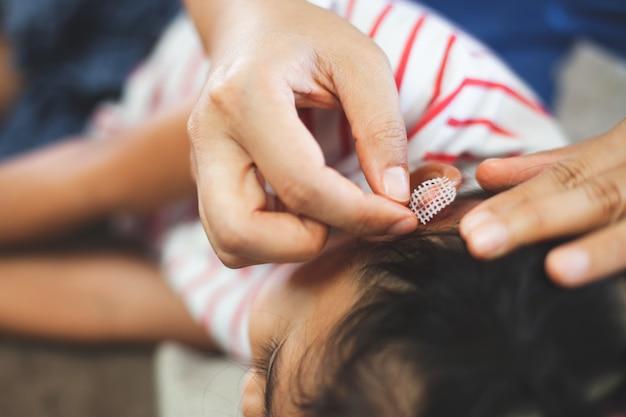 Ouder helpt haar kind bij het uitvoeren van een eerste hulp oorblessure nadat zij een ongeluk heeft gehad Premium Foto