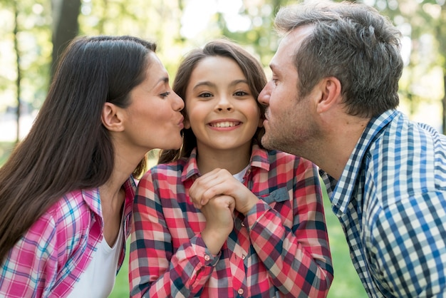 Ouder kussen hun schattige dochter in de tuin Gratis Foto