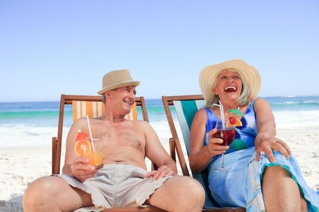 Ouder paar zittend op ligstoelen Premium Foto