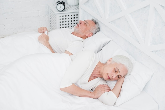 Oudere koppelslaap op een wit bed Gratis Foto