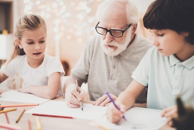 Oudere kunstenaar leert kleinkinderen om te tekenen. Premium Foto