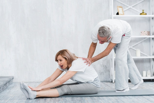 Oudere man die zijn vrouw helpt om yogapositie te doen Gratis Foto